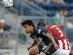 Carlos Ruiz, left of the Philadelphia Union heads the ball blocking out Heath Pearce of Chivas USA. The Union won 3-2 and lead the Eastern Conference.