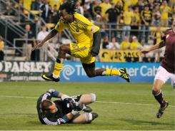 Andres Mendoza (10) of the Columbus Crew leaps over Rapids goalkeeper Matt Pickens, scoring his second goal of the night, and putting him within one of the league lead.