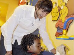 The Minnesota Timberwolves' Ricky Rubio helps three-year-old Taj McPherson build a new bear at the Build-A-Bear store in the Mall of America on Saturday in Bloomington, Minn. McPherson's family recently lost their home in a tornado.