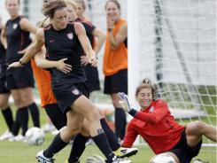 Abby Wambach, center, shoots past teammate Hope Solo, right, during a Tream USA training in Dresden, Germany, on Saturday.