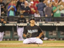 Florida Marlins relief pitcher Steve Cishek kneels at home plate after throwing a wild pitch while trying to intentionally walk Carlos Peguero of the Seattle Mariners, allowing Dustin Ackley to score from third in the 10th inning in Seattle.