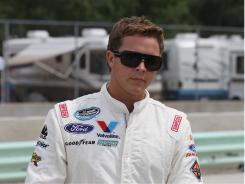Trevor Bayne walks to his car for qualifying for the Nationwide series Bucyrus 200 at Road America in Elkhart Lake, Wisconsin.
