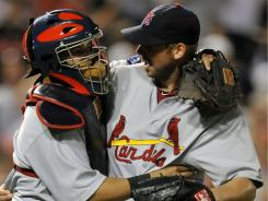 Cardinals starting pitcher Chris Carpenter, right, is congratulated by Yadier Molina after his complete game against the Orioles. The Cardinals defeated the Orioles, 5 - 1, in Baltimore on Wednesday.