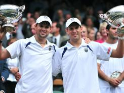 Bob, left, and  Mike Bryan show off the hardware after winning the Wimbledon men's doubles championship.