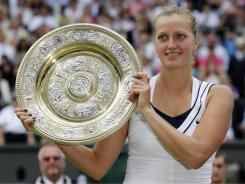 Petra Kvitova of the Czech Republic shows off her prize after she defeated Maria Sharapova of Russia on Saturday at Wimbledon to claim her first Grand Slam title.