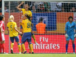 Members of the team form Sweden celebrate the first and what proved to be the winning goal of their Group C match against North Korea. Sweden won 1-0.