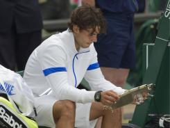 Nadal studies his runner-up prize after falling to Novak Djokovic in the Wimbledon final on Sunday.