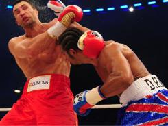 Wladimir Klitschko, left, avoids a punch from David Haye during the title fight Saturday in Hamburg, Germany. Haye suffered a lopsided loss and blamed a broken toe for his uninspired performance.