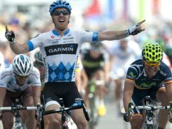 U.S. Tyler Farrar celebrates as he crosses the finish line with Spain's Jose Joaquin Rojas, right, and France's Sebastien Hinault, left, after winning the third stage of the Tour de France.
