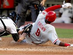 The Phillies' Dom Brown (9) slides home to score the winning run in a controversial play. Replays showed catcher John Buck made the tag in time.