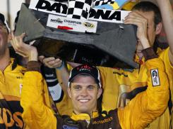 David Ragan holds up the winner's trophy as he celebrates after winning the NASCAR Coke Zero 400 auto race at Daytona International Speedway.