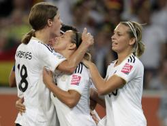 Germany's Inka Grings, center, celebrates her team's third goal with teammates Lena Goessling, right, and Kerstin Gareferekes during the Group A match against France at the Women's Soccer World Cup in Moenchengladbach, Germany on Tuesday.