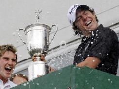 Rory McIlroy is sprayed with champagne while holding  the U.S. Open trophy at Holywood Golf Club during a celebration at his home in Holywood, Northern Ireland.