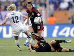 New Zealand's Betsy Hassett, left, and New Zealand's Katie Hoyle vie for the ball with Mexico's Guadalupe Worbis, on the ground and  Veronica Perez during the Group B game between New Zealand and Mexico at the World Cup in Sinsheim, Germany on July 5.