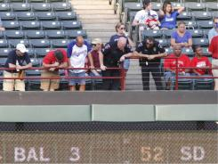 Police and fans look over the railing at Rangers Ballpark where a fan fell to his death  on Thursday.