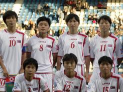 North Korea's Jo Yun Mi, Kim Su Gyong,  Paek Sol Hui, Ri Ye Gyong, goalkeeper Hong Myong Hui, Kim Un Ju, from top left, and from bottom left, Ho Un Byol, Jon Myong Hwa, Yu Jong Hui, Ri Un Hyang, Ra Un Sim pose for a team photo prior to the group C match between North Korea and Colombia on July 6.