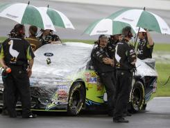 Carl Edwards' crew stands under umbrellas during the rain that halted Friday's Sprint Cup qualifying. Edwards will start seventh.