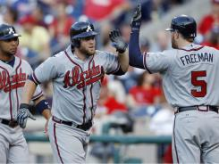 After blasting a two-run home run, Brian McCann, center, celebrates with Alex Gonzalez, left, and Freddie Freeman, right. The Braves beat the Phillies, 4-1, in 11 innings Saturday.