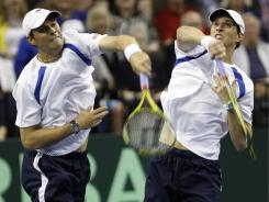 Bob Bryan, left and Mike Bryan of the USA swing at an overhead ball against Fernando Verdasco and Marcel Granollers of Spain during the Davis Cup quarterfinals Saturday in Austin.