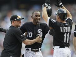 Alexei Ramirez, center, celebrates with Jake Peavy and Omar Vizquel after getting the game-winning hit during the ninth inning Saturday's game against the Twins. The White Sox won, 4-3, their first against the Twins in seven chances this season.