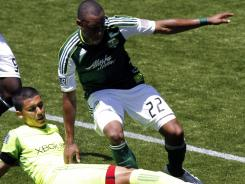 Seattle Sounders midfielder Mauro Rosales, left, and Portland Timbers defender Rodney Wallace battle for the ball during their match Sunday. The Sounders beat the Timbers 3-2 to extend their undefeated streak to eight games.