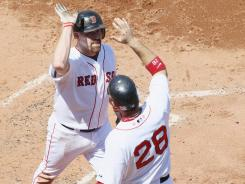 Kevin Youkilis, here congratulated by Red Sox teammate Adrian Gonzalez (28), hit one of three home runs in the second inning to help Boston to an 8-6 win.