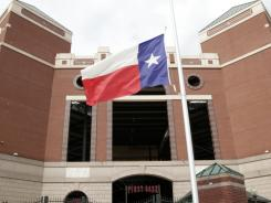 Baseball fans wait for the gates to open to the Rangers Ballpark in Arlington as a Texas flag sits at half staff before the game against the Athletics on Saturday. The flags around the ballpark have been lowered in remembrance of a fan, Shannon Stone, who fell at Thursday night's game and later died.