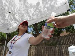 Jule De Anda hands out water in Phoenix, where the high temperatures of 100-101 degrees this weeks are actually about 7 degrees below normal for this time of year.