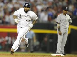 The NL's Prince Fielder rounds the bases after hitting a three-run home run in the fourth inning while the AL's Robinson Cano watches.