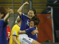 Japan's Homare Sawa, center, gets a hug and a lift from teammate Nahomi Kawasumi after Sawa scored the go-ahead goal against Sweden in the second half.