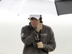 Rory McIlroy of Northern Ireland seeks shelter from the rain during the first day of the British Open.
