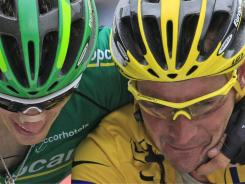 Thomas Voeckler of France, right, is congratulated by his teammate Pierre Roland of France, as he retains the overall leader's yellow jersey after crossing the finish line of the 12th stage of the Tour on Thursday.