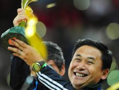 Coach Norio Sasaki celebrates with the  World Cup after Japan's victory on Sunday.