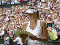 Maria Sharapova looks at her runner-up trophy after being defeated by Petra Kvitova in the Wimbledon women's singles final on July 2.