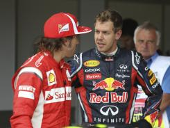 Formula One points leader Sebastian Vettel, right, talks to Spain's Fernando Alonso, third in points, prior to the July 10 British Grand Prix. Both drivers will race in German Grand Prix on Sunday.
