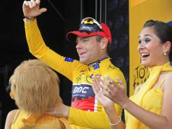 New overall leader Cadel Evans throws flowers to fans on the podium of the 20th stage of the Tour de France cycling race, an individual time trial. Evans is set to become the first Australian to win the race.