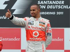 Lewis Hamilton celebrates on the podium at the Nuerburgring circuit after winning the German Grand Prix.