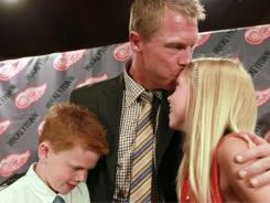 Kris Draper, kisses his daughter Kennedi, right, while embracing his son Kienan after announcing his retirement.