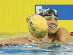 Dana Vollmer of the U.S. celebrates with Australia's Alicia Coutts after winning the women's 100-meter butterfly final at the FINA Swimming World Championships in Shanghai on Monday.
