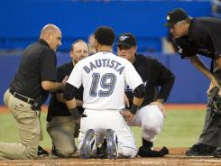 Jose Bautista speaks with the Blue Jays' medical staff after taking a pitch off his helmet.