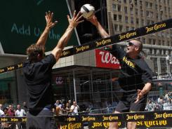 Kevin Love, right, and pro beach volleyball player John Hyden spar at the net on a court in New York's Times Square on Tuesday.