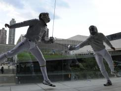 Fencers Jeff Spear (left) and Tim Morehouse teach spectators about the sport during a fencing exhibition on a terrace at Alice Tully Hall at Lincoln Center in New York City on Tuesday. They were taking part in a one-year-out program to the London 2012 Olympic and Paralympic Games.