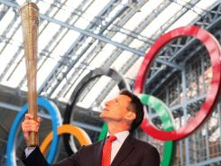 Sebastian Coe, chairman of the London 2012 Olympic Organizing Committee, poses with the London Olympic Torch.
