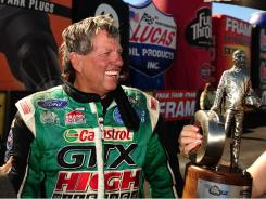 John Force celebrates after winning the Funny Car competition Sunday at the Mile High Nationals.