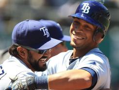 Desmond Jennings, right,  celebrates with Sean Rodriguez after helping the Rays storm back during a seven-run seventh inning against the A's on Thursday. The Rays won 10-8.
