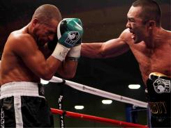WBA and IBF champion Beibut Shumenov connects with a right hand against Danny Santiago during their 12-round light-heavyweight bout Saturday night in Las Vegas. Shumenov won by ninth-round TKO.