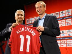 Soccer President Sunil Gulati (left) and Jurgen Klinsmann, the new head coach of the U.S. men's national team, hold up a jersey during a news conference at NikeTown on Monday in New York.