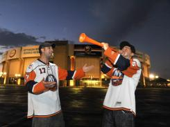 Brothers Michael and Chris Borriello wait outside the Nassau Coliseum on Long Island, N.Y., on Monday night. Nassau County residents voted down a referendum that would have backed a new hockey arena and ballpark.
