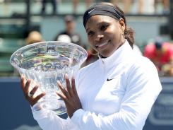 Serena Williams flashes a smile and shows off her hardware after winning the Bank of the West Classic on Sunday in Stanford, Calif.
