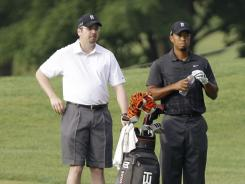 Bryon Bell gets in some work as Tiger Woods' caddie during a practice round Tuesday ahead of the WGC-Bridgestone Invitational.